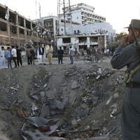 Illustrative: Afghan security forces stand next to a crater created by a massive explosion that killed over 150, according to the Afghan president, in front of the German Embassy in Kabul, Afghanistan, on May 31, 2017. The Taliban's second in command and head of the Haqqani denied Afghanistan's accusation that it was behind the bombing. (AP Photo/Rahmat Gul, File)