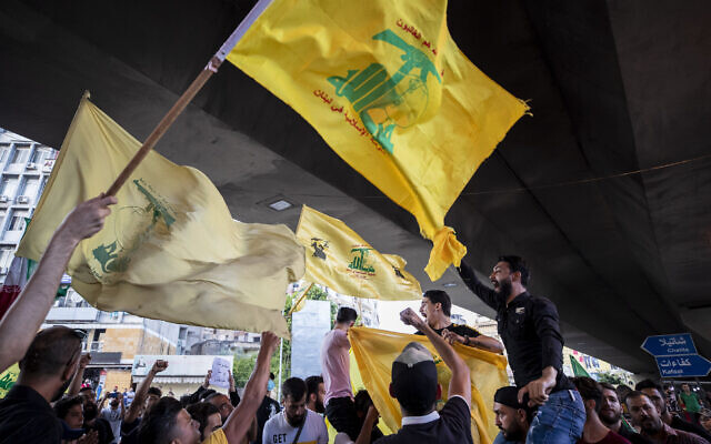 Illustrative: Hezbollah and Amal supporters wave Hezbollah and Iranian flags as they shout slogans against Israel and the US during a protest in the southern suburb of Beirut, Lebanon, June 28, 2020. (AP Photo/Hassan Ammar)