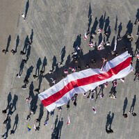 Belarusian activists cast shadows as they carry an old Belarusian flag on a rally in support of Belarus' opposition in the Independence Square in Kyiv, Ukraine, Sunday, Sept. 20, 2020. (AP Photo/Efrem Lukatsky)