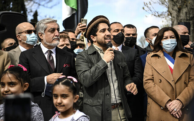 Ahmad Massoud, son of late Afghan commander Ahmad Shah Massoud, center, speaks to supporters as he is flanked by Chairman of Afghanistan's High Council for National Reconciliation Abdullah Abdullah, left, and Paris Mayor Anne Hidalgo on the sidelines of a commemoration to honor late Afghan anti-Taliban commander Massoud in an alley along the Champs Elysees Avenue in Paris, March 27, 2021. (Christophe Archambault/Pool Photo via AP)