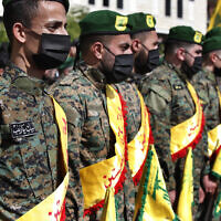 Illustrative: Hezbollah fighters attend the funeral procession on May 15, 2021, of their comrade Mohammed Tahhan who was shot dead by Israeli forces along the Lebanon-Israel border, in the southern village of Adloun, Lebanon. (AP Photo/ Mohammed Zaatari)