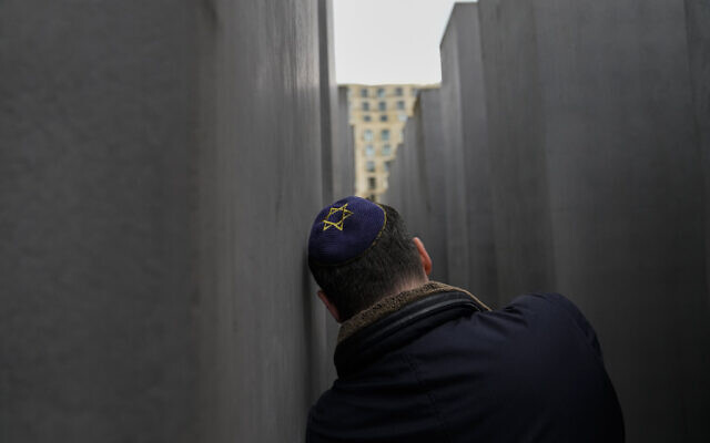 A man with a skullcap takes a photo at the Holocaust Memorial in Berlin, Germany, on Thursday, May 27, 2021. (AP Photo/Markus Schreiber)
