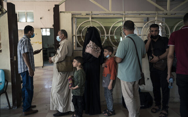 Palestinians wait in line to have their documents checked before crossing the Rafah border with Egypt, southern Gaza Strip, Sunday, June 6, 2021. (AP Photo/Felipe Dana)