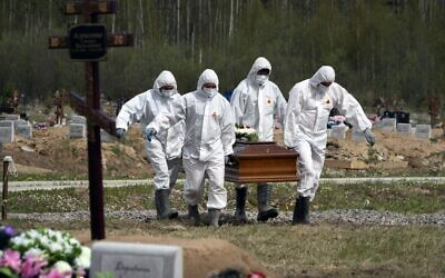 Gravediggers in protective suits carry the coffin of the deceased, who died of COVID-19, as relatives and friends stand at a distance in the coronavirus section of a cemetery in Kolpino, outside St. Petersburg.  (AP Photo/Dmitri Lovetsky, File)