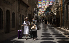 Women, one wearing a mask as a measure of protection against the coronavirus, stroll in Jerusalem, July 16, 2021. (AP Photo/Maya Alleruzzo)