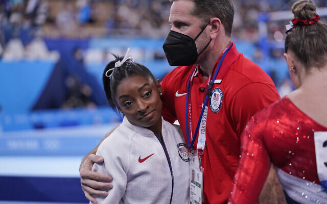 Coach Laurent Landi embraces Simone Biles, after she exited the team final, at the 2020 Summer Olympics, July 27, 2021, in Tokyo. (AP/Gregory Bull)