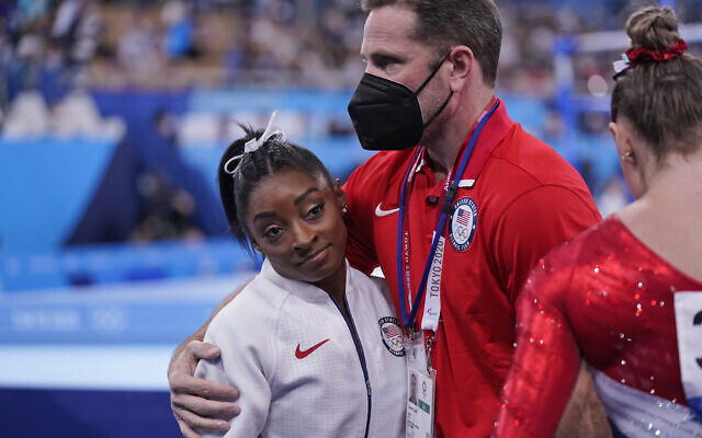 Coach Laurent Landi embraces Simone Biles, after she exited the team final with apparent injury, at the 2020 Summer Olympics, July 27, 2021, in Tokyo. (AP Photo/Gregory Bull)