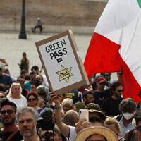 In this , Tuesday, July 27, 2021 file photo, people gather to protest against the COVID-19 vaccination pass in Rome. Protesters in Italy and in France have been wearing yellow Stars of David, like the ones Nazis required Jews to wear to identify themselves during the Holocaust. Some carry signs likening vaccine passes to  dictatorships. (AP Photo/Riccardo De Luca)