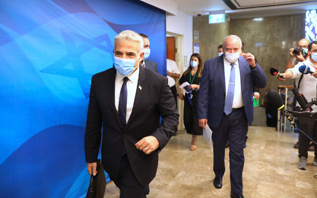 Foreign Minister Yair Lapid, left, and Finance Minister Avigdor Lieberman, right, attend a cabinet meeting at the Prime Minister's Office in Jerusalem, August 1, 2021. (Abir Sultan/Pool Photo via AP)