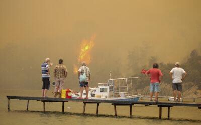 Tourists wait to be evacuated from smoke-engulfed Mazi area as wildfires rolled down the hill toward the seashore, in Bodrum, Mugla, Turkey, Sunday, Aug. 1, 2021. (AP Photo/Emre Tazegul)