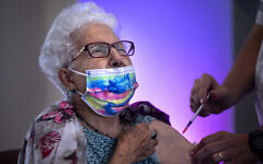 Rachel Gershon, 83, receives a third Pfizer-BioNTech COVID-19 vaccine from a Magen David Adom national emergency service volunteer, at a private nursing home, in Netanya, August 1, 2021. (AP Photo/Oded Balilty)