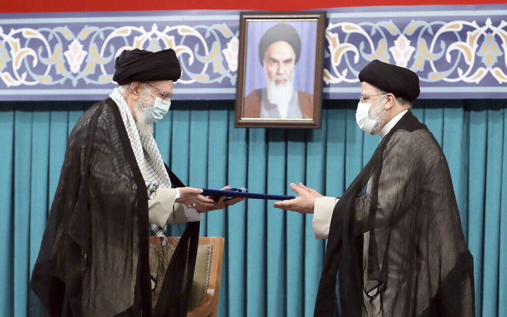 Iran's Supreme Leader Ayatollah Ali Khamenei, left, gives his official seal of approval to newly elected President Ebrahim Raisi in an endorsement ceremony in Tehran, Iran, August 3, 2021. (Office of the Iranian Supreme Leader via AP)