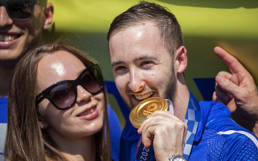 Artem Dolgopyat, Israeli artistic gymnastics men's gold medalist, stands with his fiancée Maria Sakovich, on his arrival at Ben Gurion Airportl, August 3, 2021. (AP Photo/Ariel Schalit)
