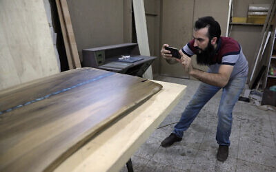 Ali Hedieloo takes a photo of his product to post on social media at his furniture workshop in the southern suburbs of Tehran, Iran, July 30, 2021. (AP Photo/Vahid Salemi)