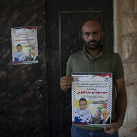 """Moayyad al-Alami, father of Mohammed al-Alami, 12, carries a poster with picture and name of his son and reads """"Palestinian National Liberation movement, Fatah, offers her hero martyr child,"""" at the family house, in the West Bank village of Beit Ummar, near Hebron, August 4, 2021. (AP/Nasser Nasser)"""