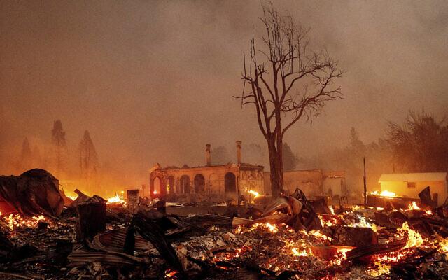 Buildings burn as the Dixie Fire tears through the Greenville community of Plumas County, California, on Wednesday, Aug. 4, 2021 (AP Photo/Noah Berger)