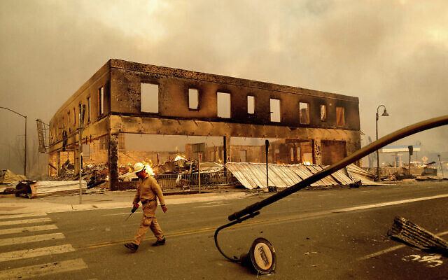 Operations Chief Jay Walter passes the historic Sierra Lodge as the Dixie Fire burns through the Greenville community of Plumas County, California, on  Aug. 4, 2021 (AP Photo/Noah Berger)