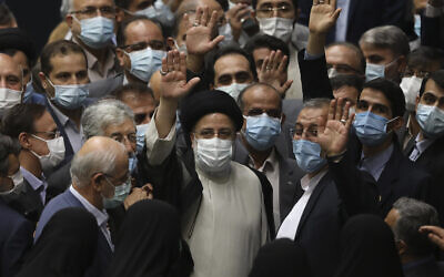 President Ebrahim Raisi, center, waves to journalists as he is surrounded by group of lawmakers after taking his oath as president at the parliament in Tehran, Iran, on Thursday, August 5, 2021. (AP Photo/Vahid Salemi)