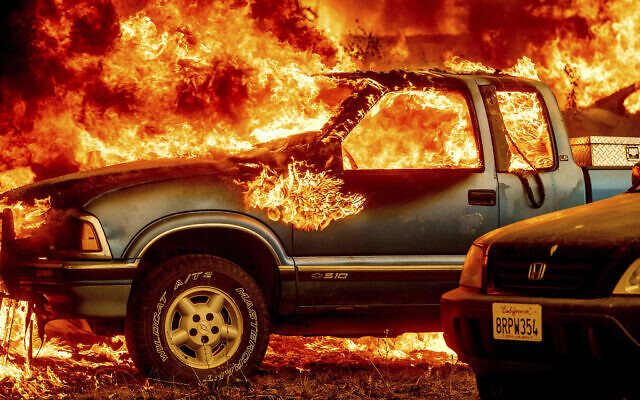 Flames from the Dixie Fire consume a pickup truck on Highway 89 south of Greenville on Aug. 5, 2021, in Plumas County, California. (AP Photo/Noah Berger)