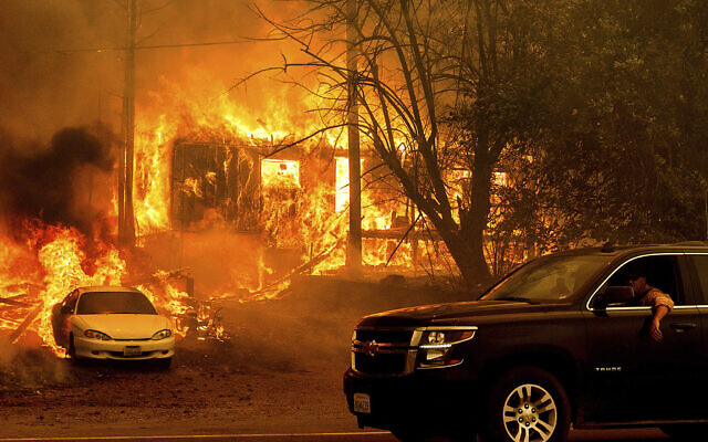 Flames from the Dixie Fire consume a home on Highway 89 south of Greenville on Aug. 5, 2021, in Plumas County, Calif. (AP Photo/Noah Berger)