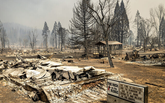 A church marquee stands among buildings destroyed by the Dixie Fire in Greenville on Aug. 5, 2021, in Plumas County, California (AP Photo/Noah Berger)