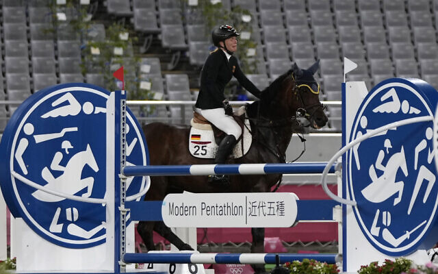 Annika Schleu of Germany cries as she couldn't controls her horse to compete in the equestrian portion of the women's modern pentathlon at the 2020 Summer Olympics, on August 6, 2021, in Tokyo, Japan. (AP Photo/Hassan Ammar)