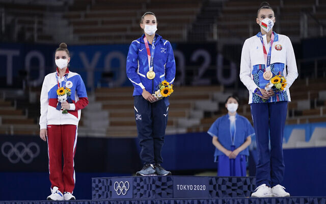From left, silver medalist Dina Averina, of Russian Olympic Committee, gold medalist Linoy Ashram, of Israel, and bronze medalist Alina Harnasko, of Belarus, stand on the podium after the rhythmic gymnastics individual all-around final at the 2020 Summer Olympics, on August 7, 2021, in Tokyo, Japan. (AP/Ashley Landis)