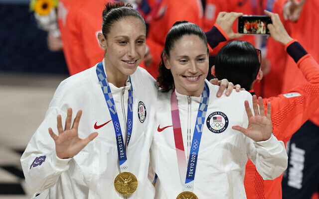 United States's Sue Bird, right, and Diana Taurasi pose with their gold medals during the medal ceremony for women's basketball at the 2020 Summer Olympics, in Saitama, Japan, August 8, 2021. (Charlie Neibergall/AP)