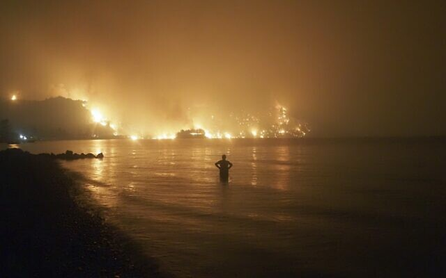 A man watches as wildfires approach Kochyli beach near Limni village on the island of Evia, about 160 kilometers (100 miles) north of Athens, Greece, August 6, 2021. (AP Photo/Thodoris Nikolaou, file)
