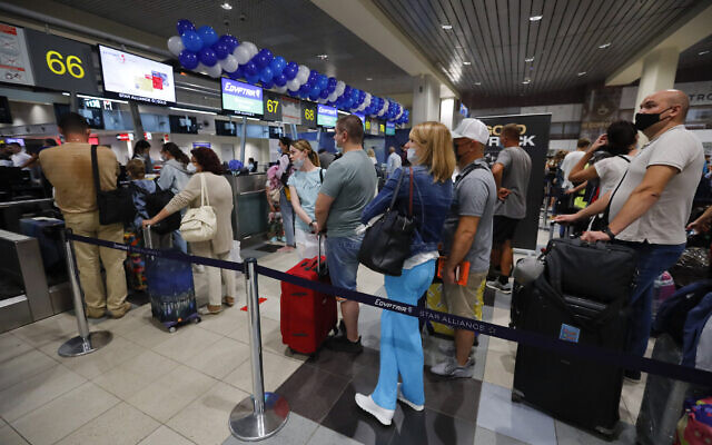 Russian tourists gather at the Egyptair check-in desk at the Domodedovo International Airport outside Moscow, Russia, August 9, 2021. (AP Photo/Alexander Zemlianichenko Jr)