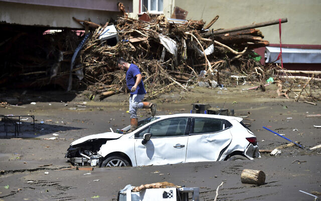 A man checks his car buried in the mud after floods and mudslides killed about three dozens of people, in Bozkurt town of Kastamonu province, Turkey, Friday, Aug. 13, 2021. (AP Photo)