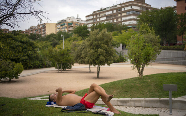 A man sunbathes in a park during a heatwave in Madrid, Spain, on August 14, 2021. (AP Photo/Andrea Comas)