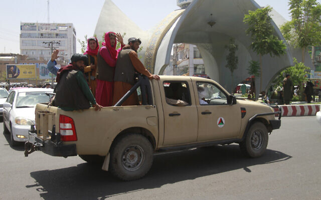 Taliban fighters pose on the back of a vehicle in the city of Herat, west of Kabul, Afghanistan, on August 14, 2021, after they took the province from Afghan government. (AP Photo/Hamed Sarfarazi)