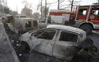 Charred cars are pictured after a fire near the village of Achlouf, in the Kabyle region, east of Algiers, August 13, 2021. (Toufik Doudou/AP)