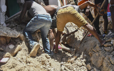 Several men work to rescue the body of a girl buried in the rubble of a house in the aftermath of an earthquake in Les Cayes, Haiti, August 14, 2021. (AP Photo / Duples Plymouth)