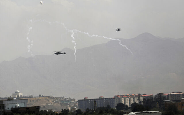 Anti-missile decoy flares are deployed as U.S. Black Hawk military helicopters and a dirigible balloon fly over the city of Kabul, Afghanistan, Sunday, Aug. 15, 2021. (AP/Rahmat Gul)