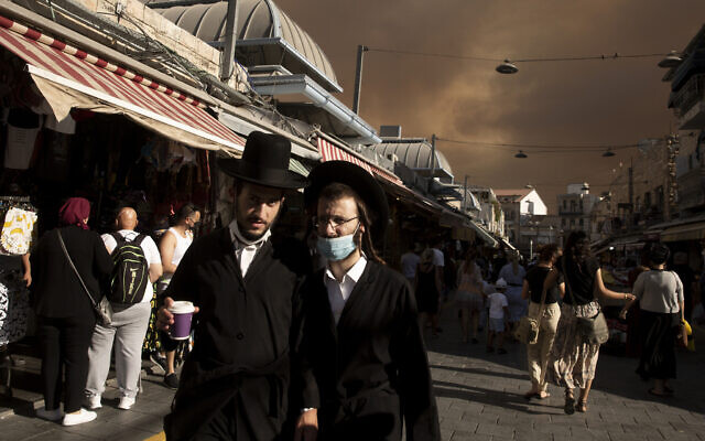 Ultra-Orthodox Jews walk through the Machane Yehuda market under a sky darkened by nearby wildfires, in Jerusalem, Aug. 15, 2021.(AP Photo/Maya Alleruzzo)