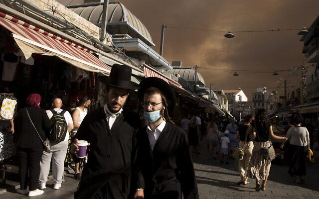 Ultra-Orthodox Jews stroll through the Machane Yehuda market under a sky darkened by nearby wildfires, in Jerusalem, August 15, 2021. (Maya Alleruzzo/AP)