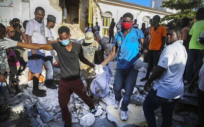People recover the body of a deceased person from the rubble of a house destroyed by the earthquake in Les Cayes, Haiti, Sunday, Aug. 15, 2021. (AP/Joseph Odelyn)
