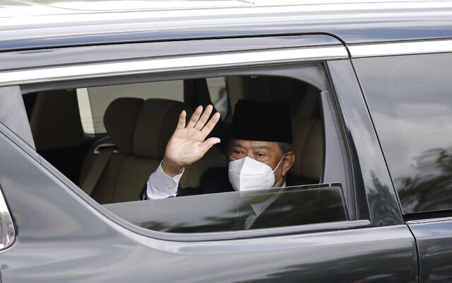 Embattled Malaysian Prime Minister Muhyiddin Yassin waves from a car while entering the National Palace to meet with the King in Kuala Lumpur, Malaysia, Aug. 16, 2021 (AP Photo/FL Wong)