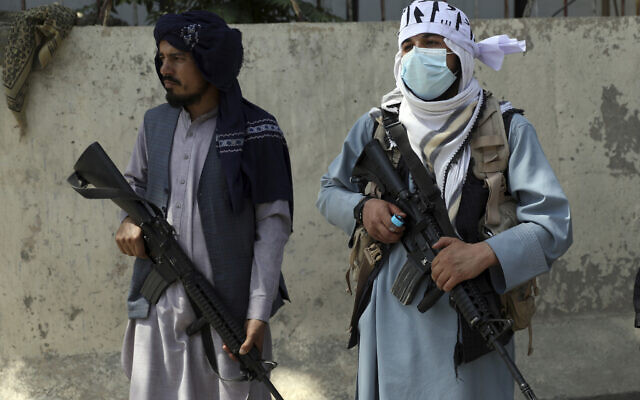 Taliban fighters stand guard in the main gate leading to Afghan presidential palace, in Kabul, Afghanistan, Monday, Aug. 16, 2021. (AP Photo/Rahmat Gul)