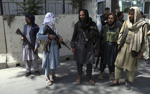 Taliban fighters stand guard at the main gate leading to the Afghan presidential palace, in Kabul, Afghanistan, Aug. 16, 2021 (AP Photo/Rahmat Gul)