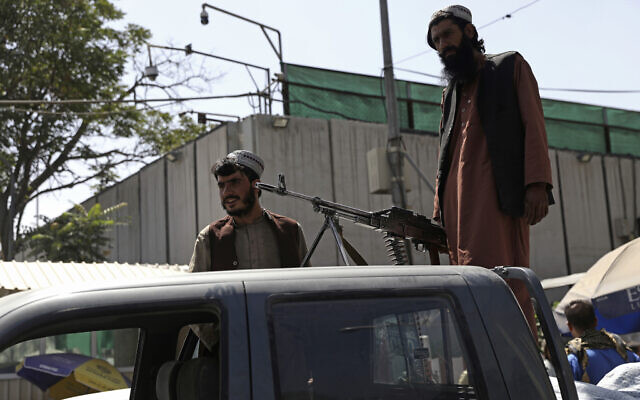 Taliban fighters stand guard on the back of vehicle with a machine gun in front of main gate leading to Afghan presidential palace, in Kabul, Afghanistan, August 16, 2021.(AP/Rahmat Gul)