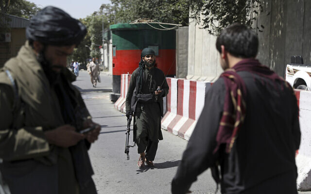 Taliban fighters stand guard at a checkpoint on the road to the Afghan foreign ministry, in Kabul, Afghanistan, August 16, 2021. (AP Photo/Rahmat Gul)