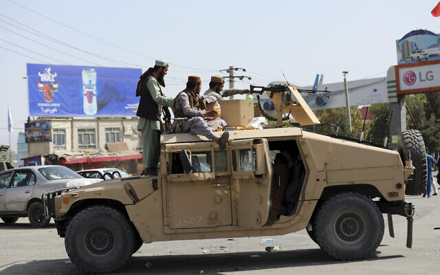 Taliban fighters stand guard in front of the Hamid Karzai International Airport, in Kabul, Afghanistan, August 16, 2021.  (AP Photo/Rahmat Gul)