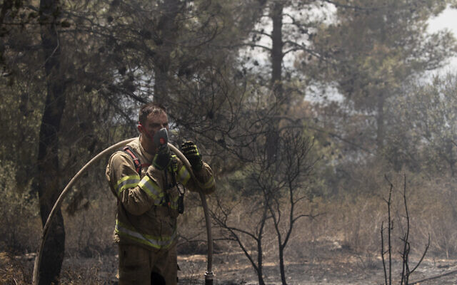 An Israeli firefighter pauses to put on a mask while battling wildfires for the second day near Shoresh, on the outskirts of Jerusalem, Aug. 16, 2021 (AP Photo/Maya Alleruzzo)