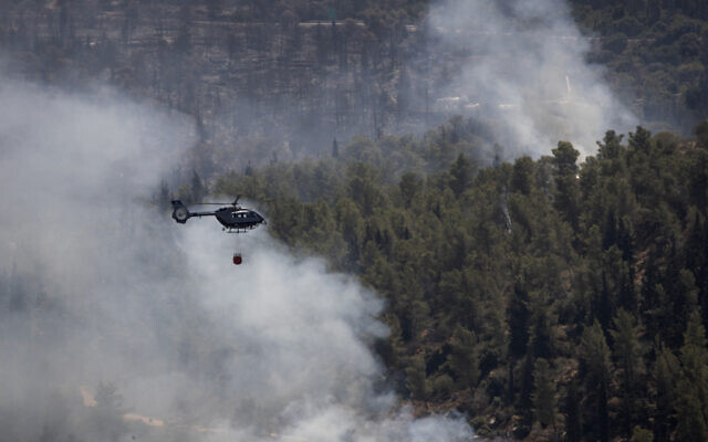 An Israeli helicopter drops water while battling the second day of wildfires near Shoresh, on the outskirts of Jerusalem, Aug. 16, 2021 (AP Photo/Maya Alleruzzo)