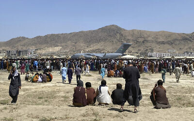 Hundreds of people gather near a US Air Force C-17 transport plane at a perimeter at the international airport in Kabul, Afghanistan, August 16, 2021. (AP Photo/Shekib Rahmani)
