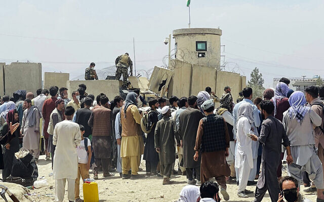 Afghan security guards stand on a wall as hundreds of people gather outside the international airport in Kabul, Afghanistan, on Tuesday, August 17, 2021. (AP)