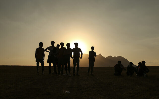 Young men who say they deserted the Afghan military and fled to Turkey through Iran stand in the countryside in Tatvan, in Bitlis Province in eastern Turkey, Tuesday, Aug. 17, 2021. (AP Photo/Emrah Gurel)